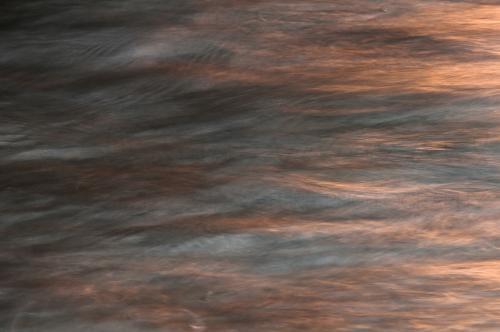 Lange sluitertijdopname van de kleuren van de zonsondergang in golven