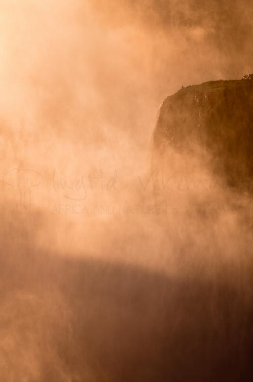 Rock in mist of water spray at Victoria Falls in Livingstone in Zambia